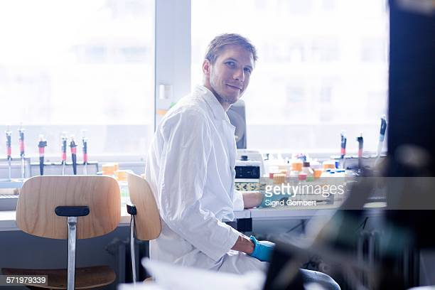 portrait of young male scientist at lab bench - sigrid gombert stock pictures, royalty-free photos & images