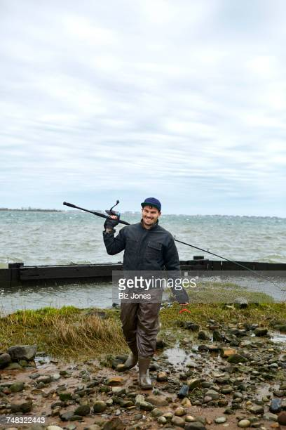 Portrait of young male sea fisher with fishing rod over his shoulder