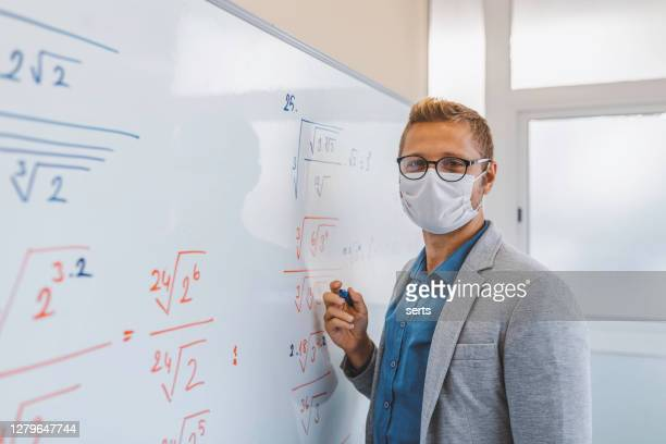 portrait of young male teacher with face mask writing on blackboard in classroom - teacher stock pictures, royalty-free photos & images