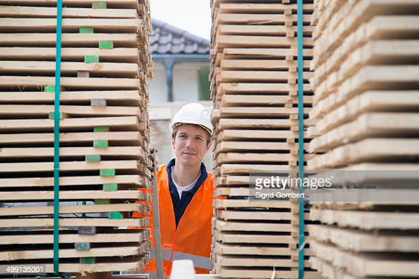 Portrait of young male worker between pallet stacks in timber yard