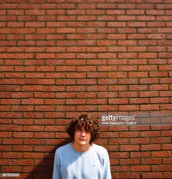 Portrait Of Young Man Against Brick Wall