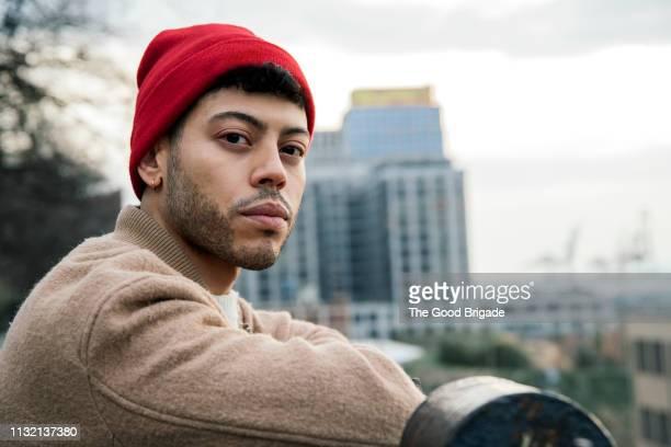 portrait of young man against city skyline - serieus stockfoto's en -beelden