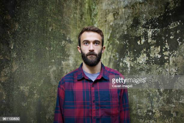 Portrait of young man against messy wall