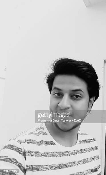 Portrait Of Young Man Against Wall At Home