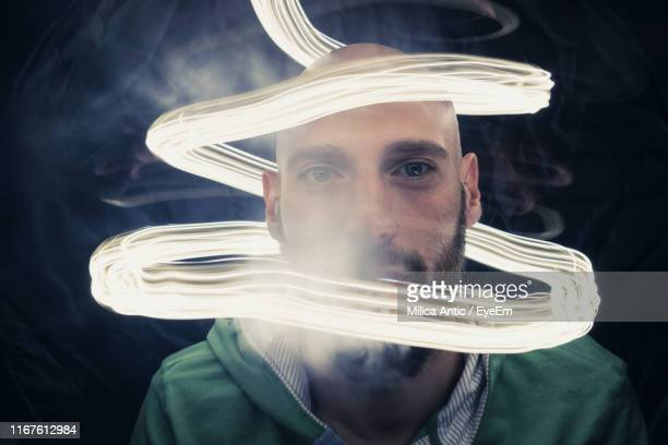 portrait of young man amid light painting and smoke over black background - lichtmalerei stock-fotos und bilder