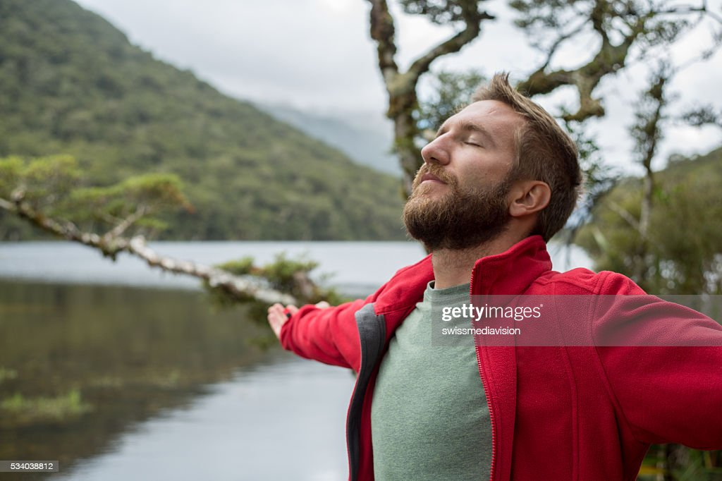 Portrait of young man arms outstretched by mountain lake : Stock Photo