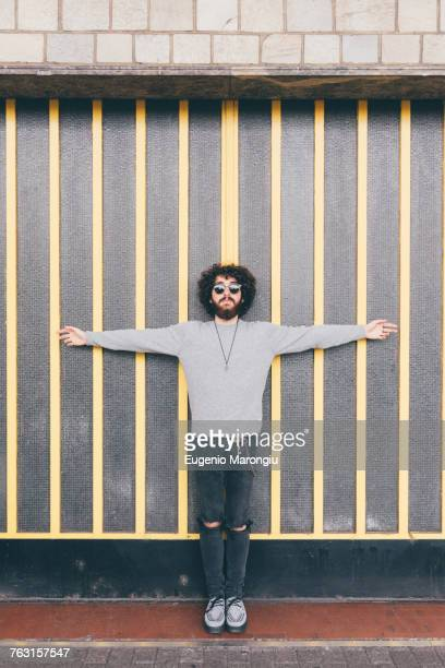 portrait of young man, arms outstretched, in urban environment - arms outstretched stock pictures, royalty-free photos & images