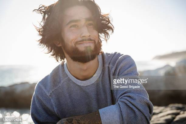 portrait of young man at beach on windy day - lifestyle stock pictures, royalty-free photos & images