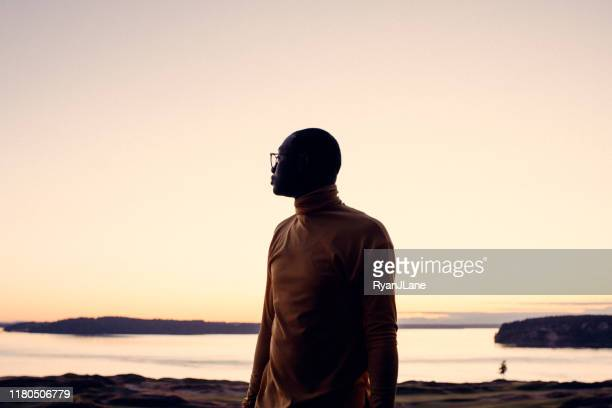 portrait of young man at sunset - moody sky stock pictures, royalty-free photos & images