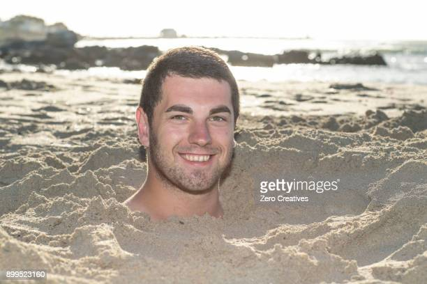 Portrait of young man buried up to his neck in sand on beach