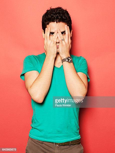 Portrait of young man covering face with hands against red background