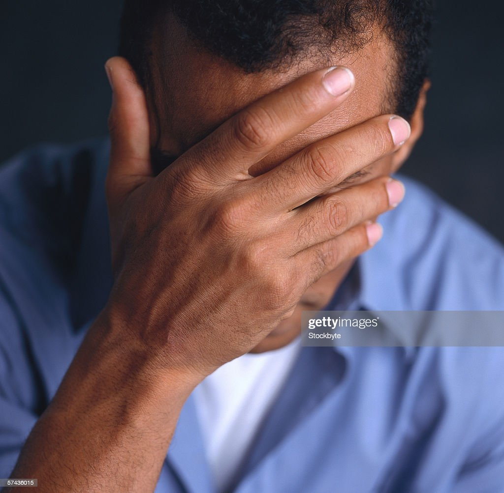portrait of young man covering face with his hand : Stock Photo