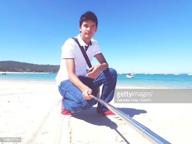 Portrait Of Young Man Crouching At Beach Against Sky