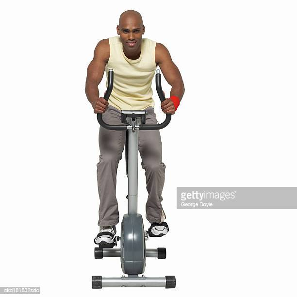 portrait of young man cycling on exercise bicycle - exercise bike stock photos and pictures