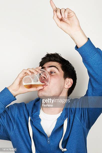 portrait of young man drinking a pint of lager - binge drinking stock photos and pictures