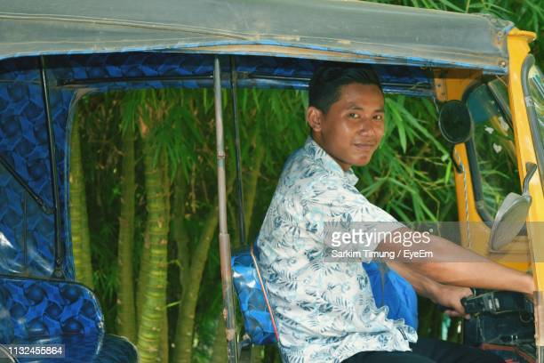 portrait of young man driving jinrikisha - rickshaw stock pictures, royalty-free photos & images