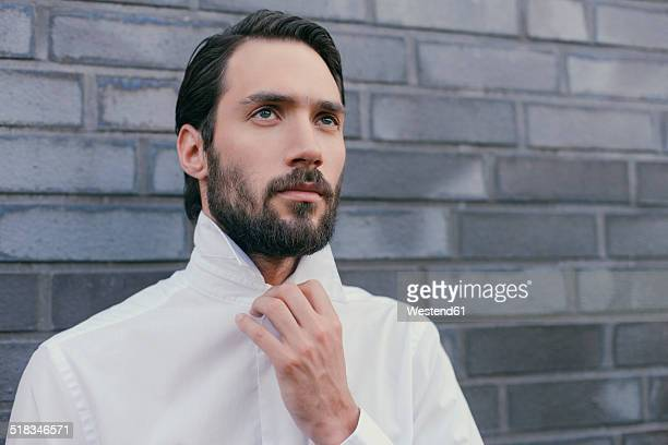 Portrait of young man folding up the collar of his shirt