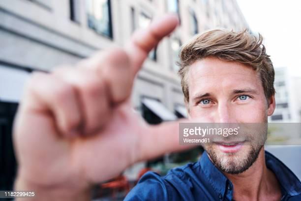 portrait of young man gesticulating - occhi azzurri foto e immagini stock