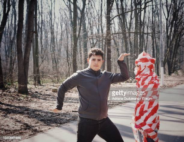 Portrait Of Young Man Gesturing By Cordon Tape Wrapped Woman On Road In Forest