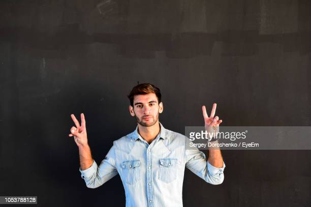Portrait Of Young Man Gesturing Peace Sign Against Wall
