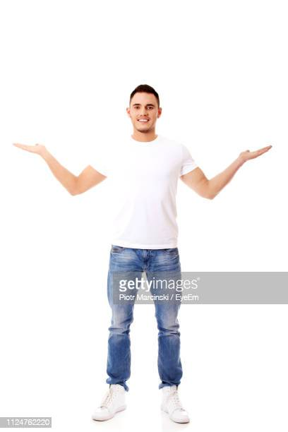 portrait of young man gesturing while standing against white background - arms outstretched stock pictures, royalty-free photos & images