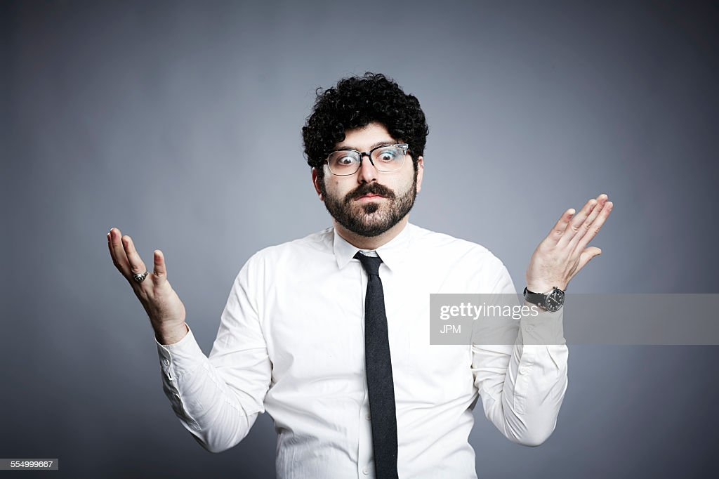 Portrait of young man, hands open in questioning expression : Stock Photo