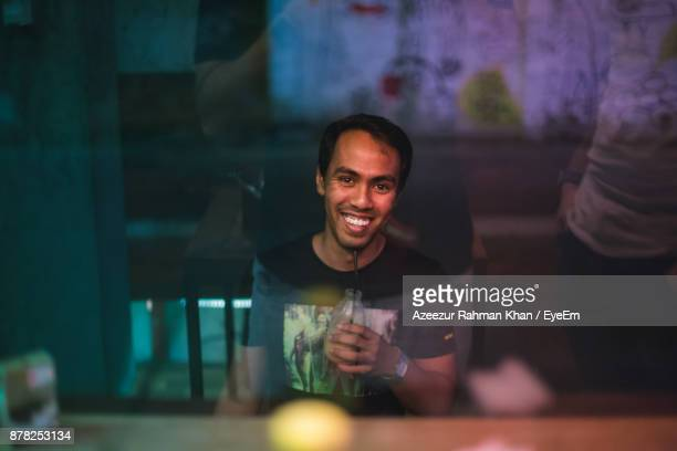 portrait of young man having drink while sitting at cafe see through window - bangladeshi man stock photos and pictures