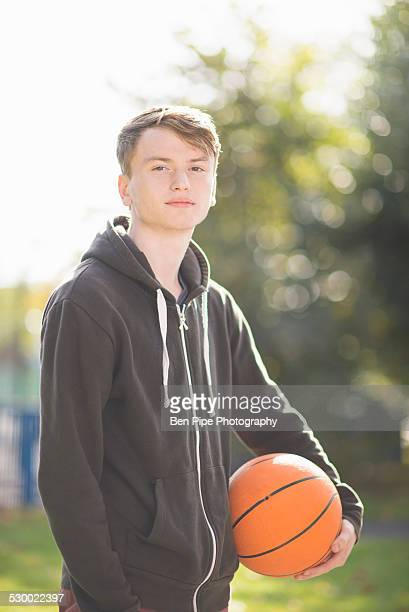 Portrait of young man holding basketball
