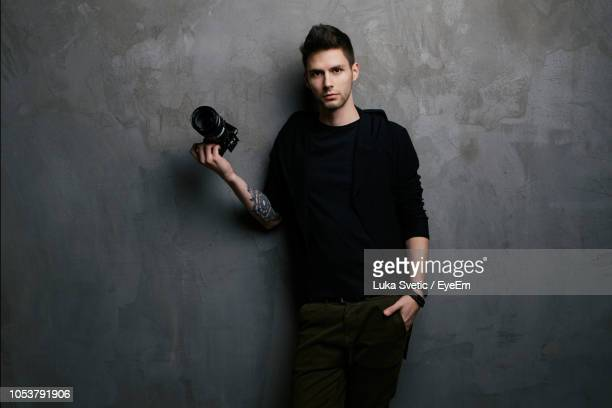 portrait of young man holding camera while standing against wall - photographer stock pictures, royalty-free photos & images
