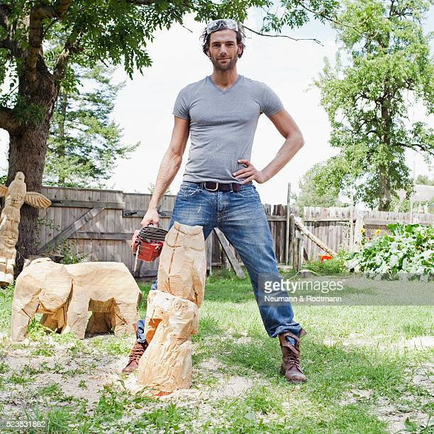 Portrait of young man holding chainsaw