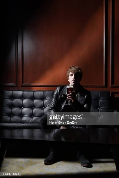 portrait of young man holding drink while sitting on sofa at home - bank zitmeubels stockfoto's en -beelden
