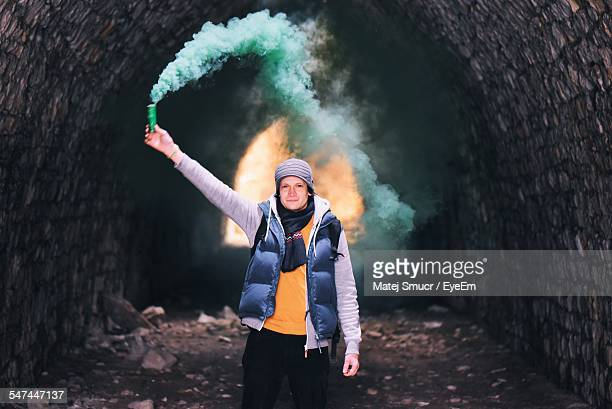 Portrait Of Young Man Holding Flare In Cave