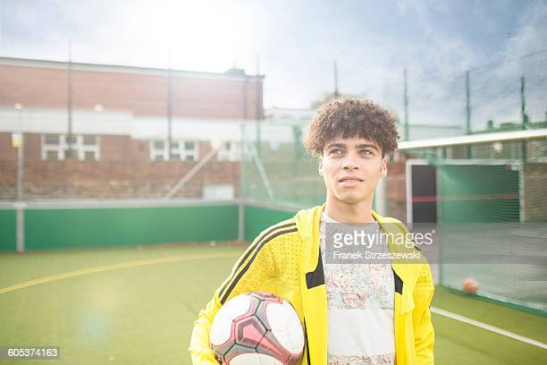 Portrait of young man holding football, on urban football pitch