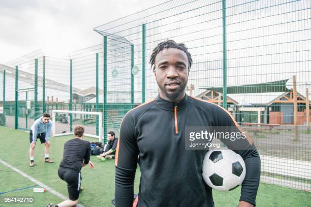 portrait of young man holding football - soccer player stock pictures, royalty-free photos & images