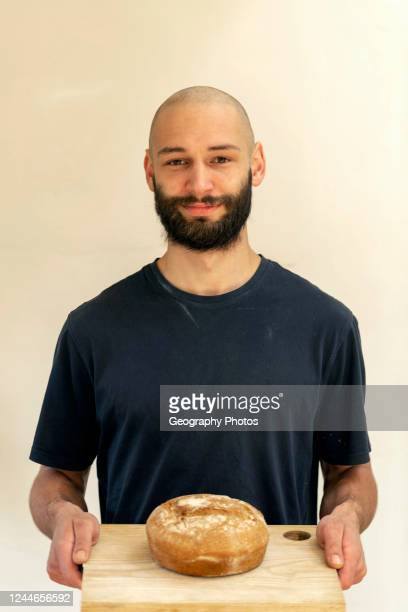Portrait of young man holding freshly baked loaf of bread during Coronavirus lockdown UK
