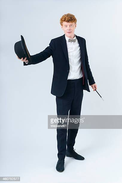 Portrait of young man holding hat and magic wand