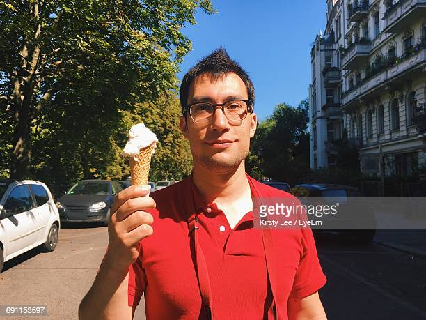 Portrait Of Young Man Holding Ice Cream Cone On Street