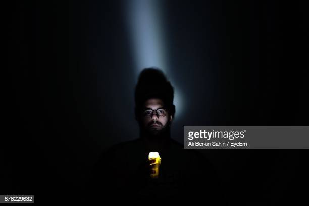 Portrait Of Young Man Holding Illuminated Flashlight In Darkroom