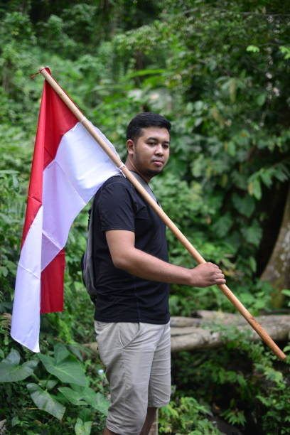 Portrait Of Young Man Holding Indonesian Flag Against Trees