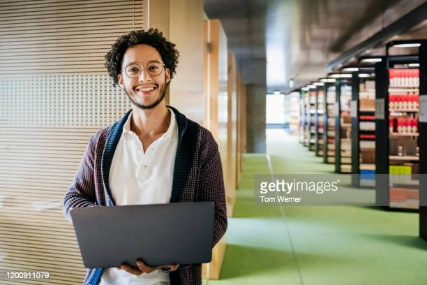portrait of young man holding laptop in library - alleen één jonge man stockfoto's en -beelden
