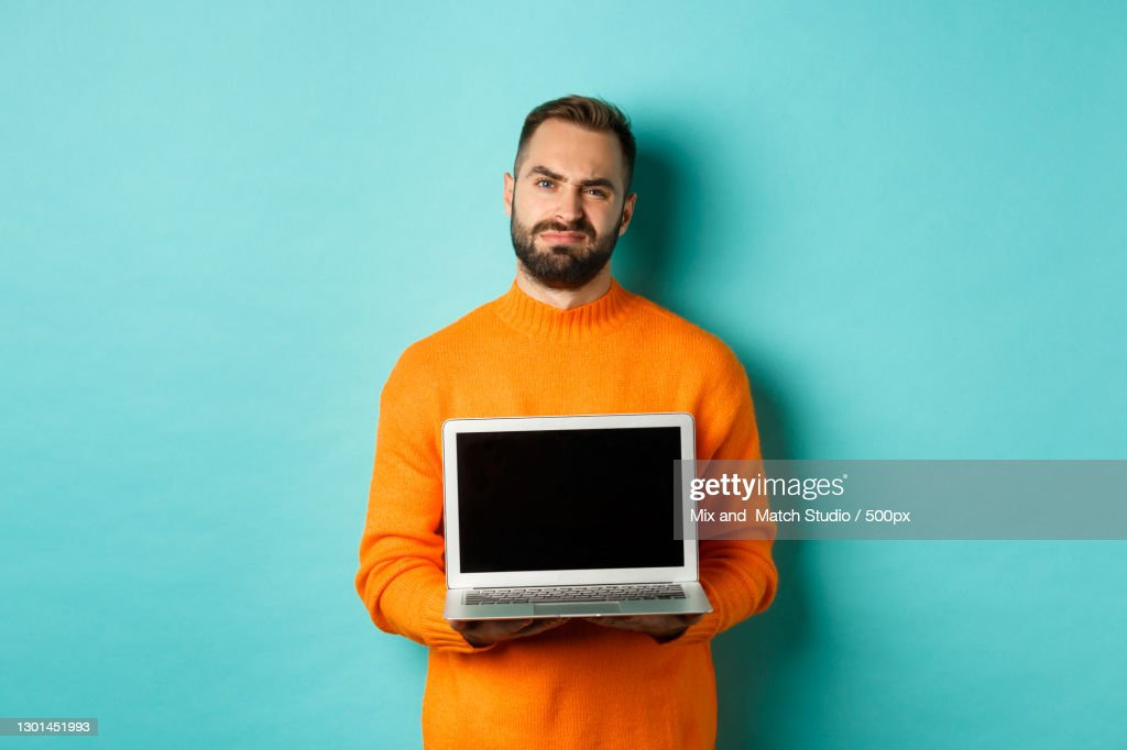 Portrait of young man holding laptop while standing against blue background : ストックフォト