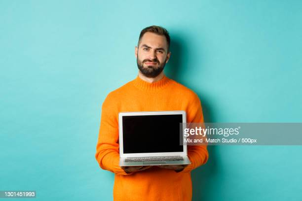 portrait of young man holding laptop while standing against blue background - オレンジ色のシャツ ストックフォトと画像