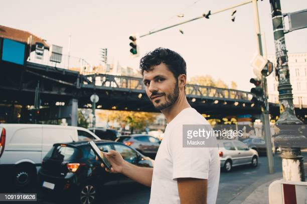 portrait of young man holding mobile phone while standing on sidewalk in city - cool cars stock pictures, royalty-free photos & images