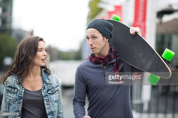 Portrait of young man holding skateboard on his shoulder while talking with his girlfriend
