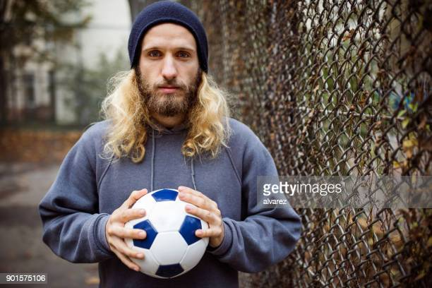 portrait of young man holding soccer ball by fence - long hair stock pictures, royalty-free photos & images