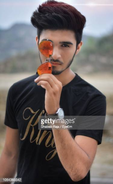 portrait of young man holding sunglasses standing on field - delhi stock pictures, royalty-free photos & images