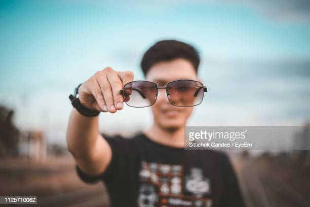 Portrait Of Young Man Holding Sunglasses While Standing Against Sky