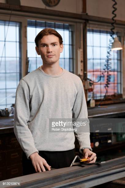 portrait of young man in blacksmith workshop - robin skjoldborg stock pictures, royalty-free photos & images