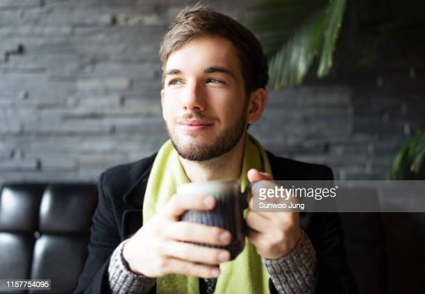 portrait of young man in cafe holding mug - ハンサム ストックフォトと画像