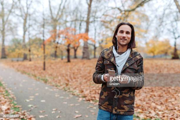 Portrait of young man in casual clothing listening to podcast